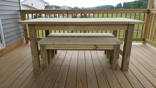 Farmhouse table with benches recessed, side view.